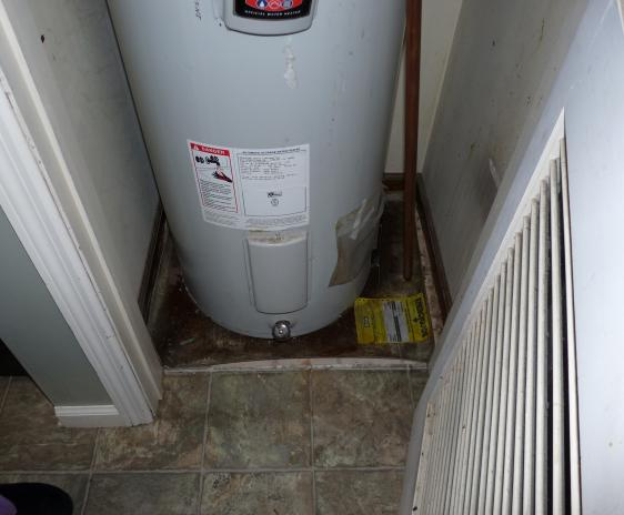 The seeping water heater (with no drain pan) in the left closet.